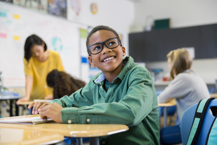 A young boy smiling in a classroom