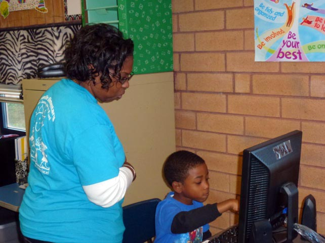 Female teacher directing young male student using a computer