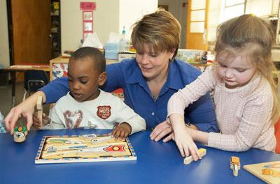 Teacher working with two children